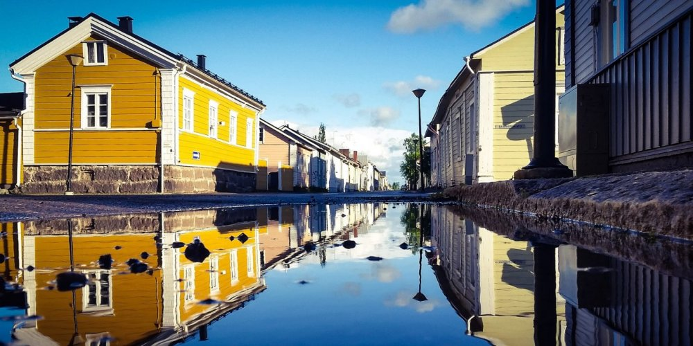 Wooden houses along Brahenkatu street. Reflection of the houses on wet street.